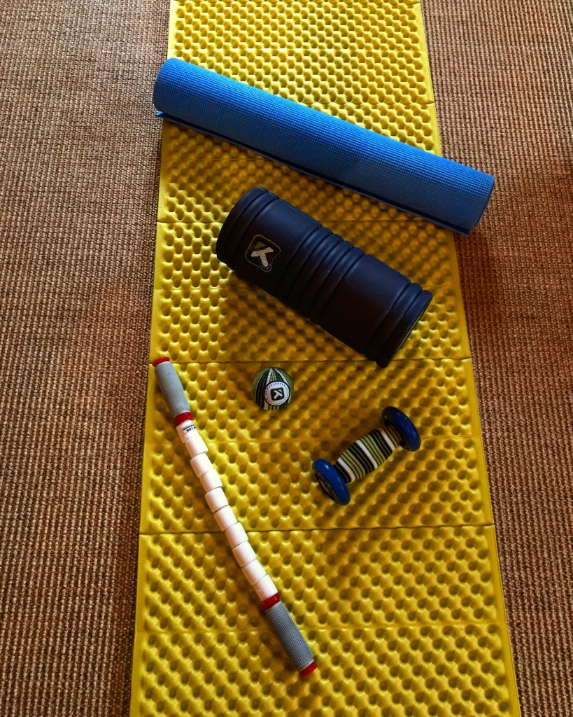 A few simple recovery tools: yoga mat, trigger point rollers, trigger point ball, massage stick